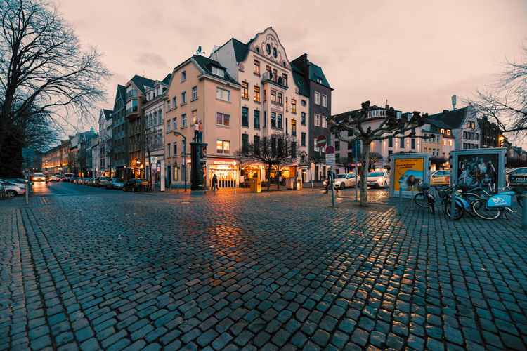 Duesseldorf, GERMANY - February 09, 2019: After heavy rain, only few pedestrants walk along a corner od the old town Building Exterior Architecture Built Structure City Building Street Sky Residential District Cobblestone Illuminated Dusk Nature Transportation Town No People Tree Mode Of Transportation Outdoors House Paving Stone