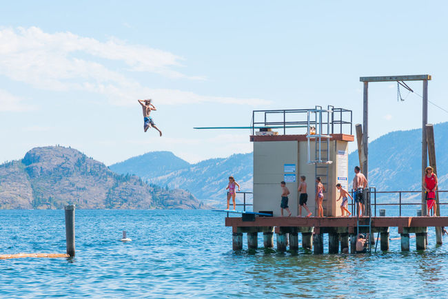 Peachland, British Columbia/Canada - August 6, 2017: a boy leaps of the dock into Okanagan Lake at Swim Bay, a popular summertime destination for tourists and locals, in the Okanagan Valley. Bright Diving Fun Happy Kids Okanagan Lake Peachland, British Columbia Swim Bay Swimming Travel Beach Canada Diving Board Diving Platform Editorial  Exhilaration Jumping Men Mountains People South Okanagan Summer Tourism Vacation Women