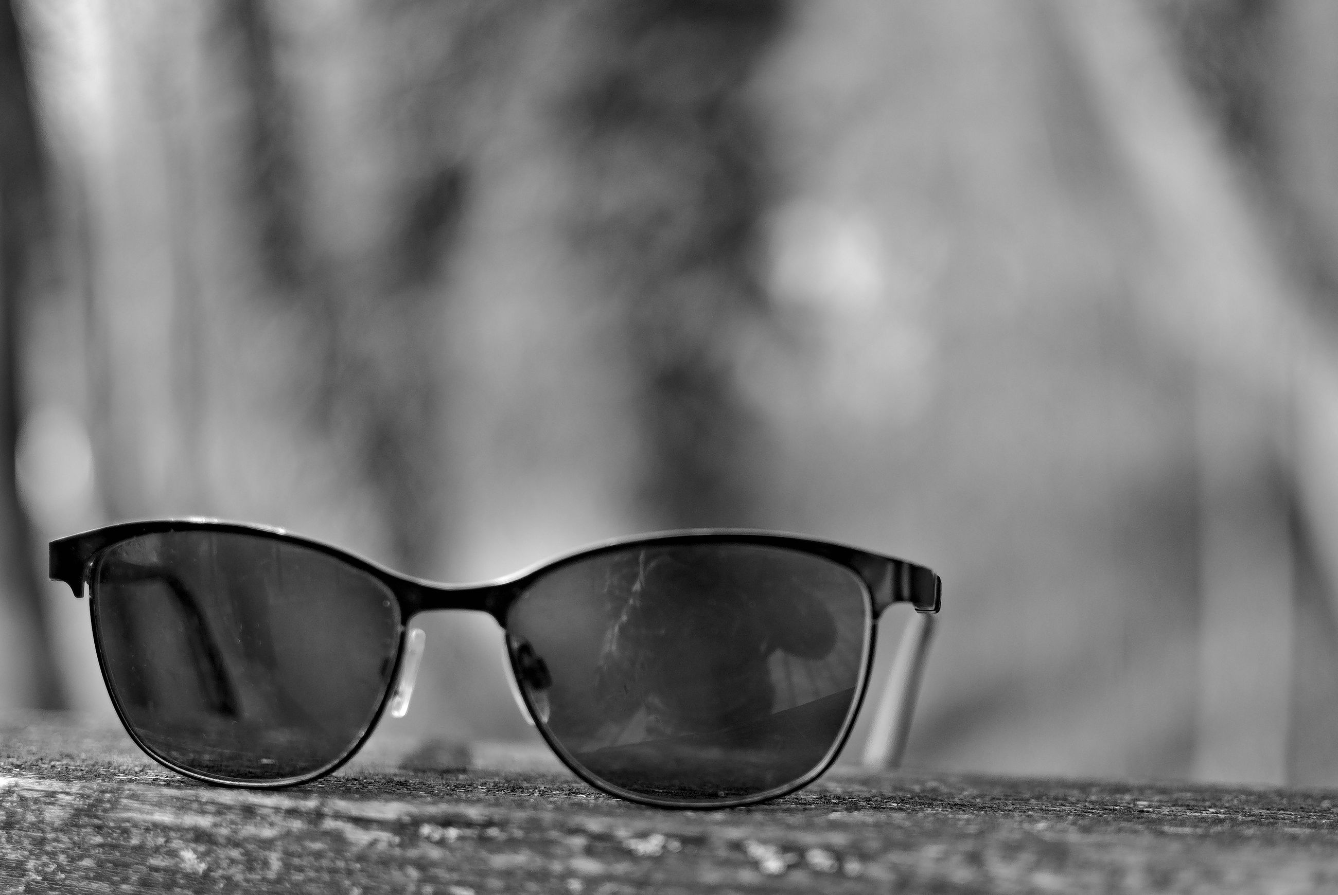 glasses, focus on foreground, fashion, sunglasses, close-up, transparent, personal accessory, eyewear, reflection, protection, still life, glass - material, security, day, eyeglasses, no people, selective focus, nature, table, outdoors, surface level