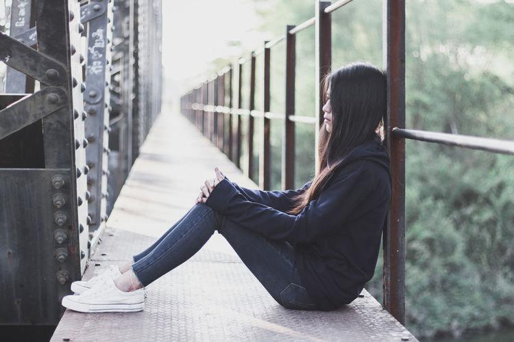Side view of sad woman sitting on bridge