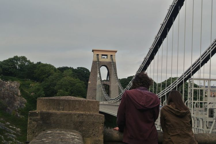 Rear view of couple on bridge against sky
