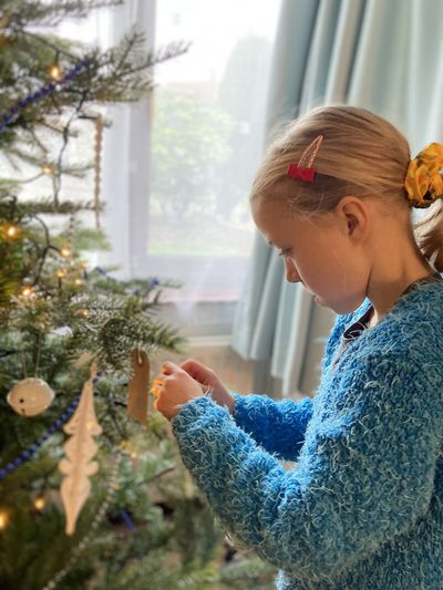 Side view of young woman wearing christmas tree