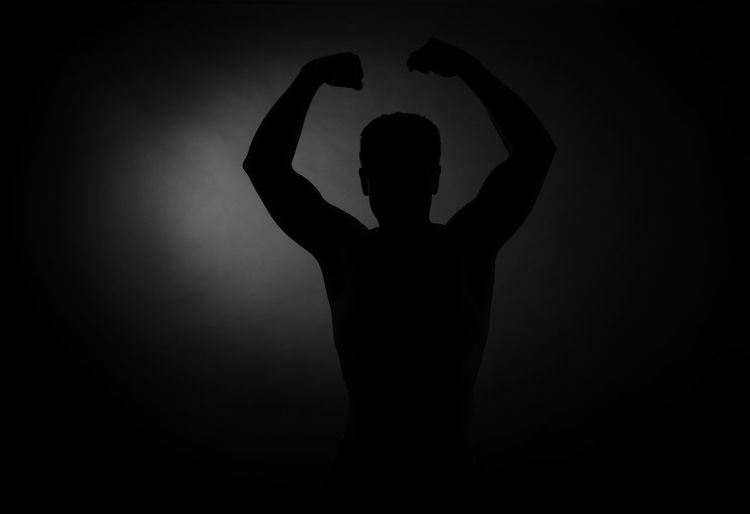 Silhouette man standing against black background