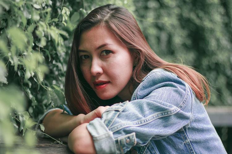 Portrait of beautiful woman by plants