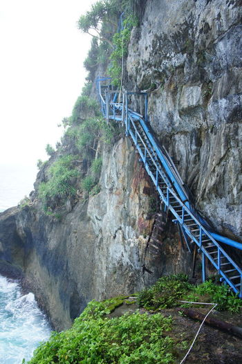 Bridge over river by cliff against sky
