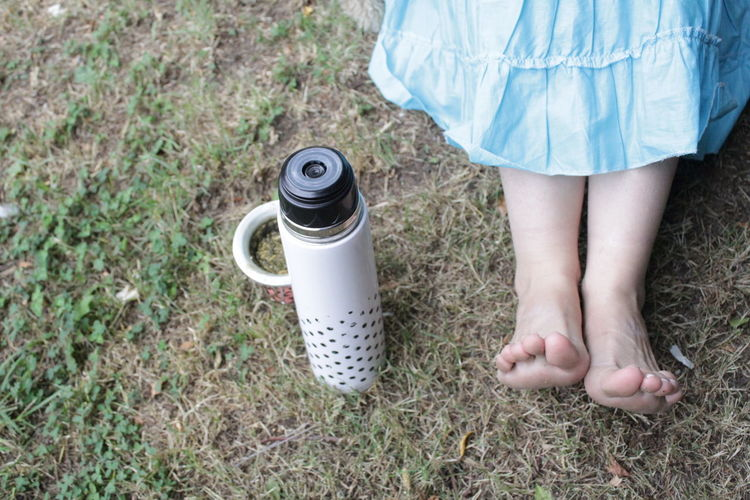 Low section of woman sitting by insulated drink container on field