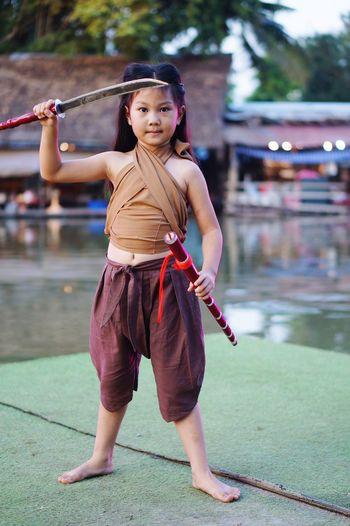 Full length portrait of girl standing outdoors