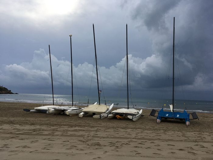 Sailboats on beach against sky