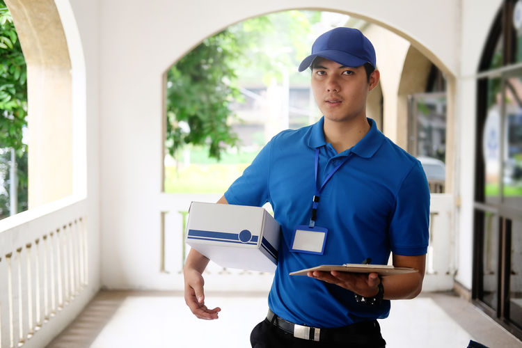 Portrait Of Delivery Man Standing With Parcel And Clipboard
