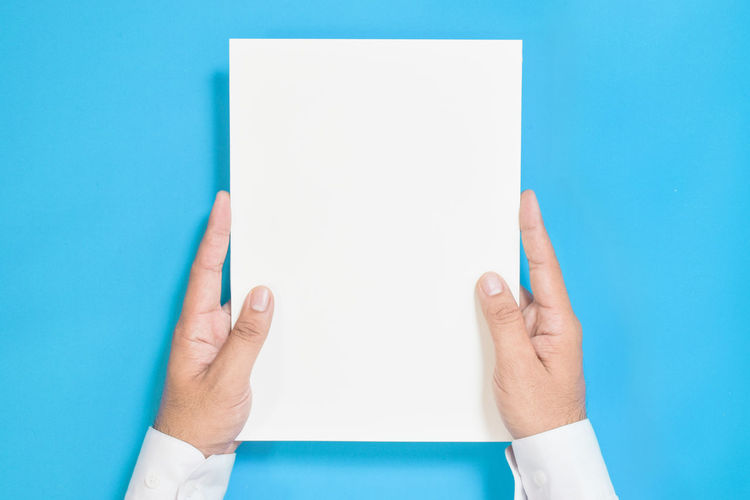 Midsection of person holding paper against blue background