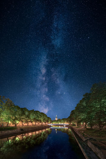 Canal by trees against sky at night