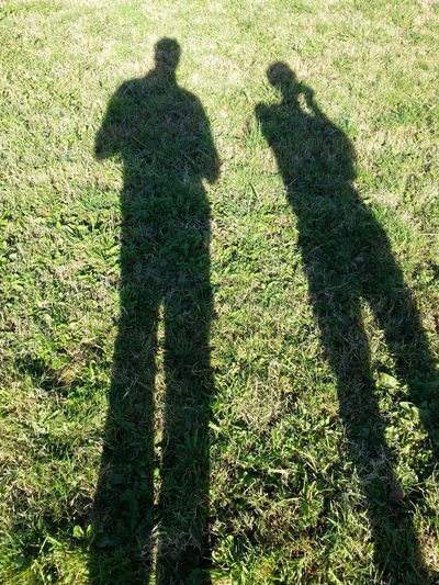 Shadow of people on grassy field