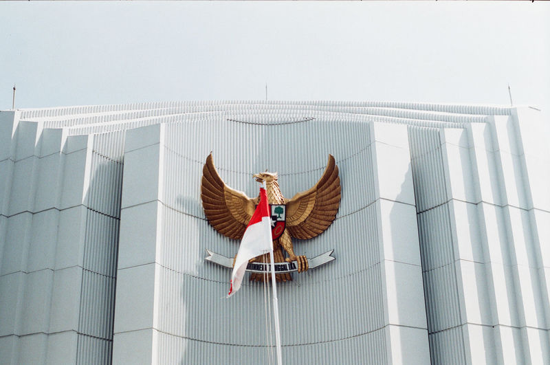 Woman sitting on roof against sky
