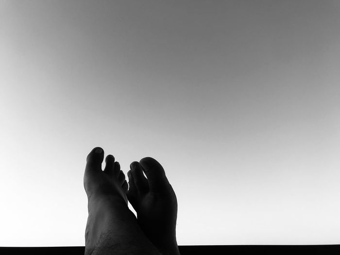Low section of man with feet up against clear sky