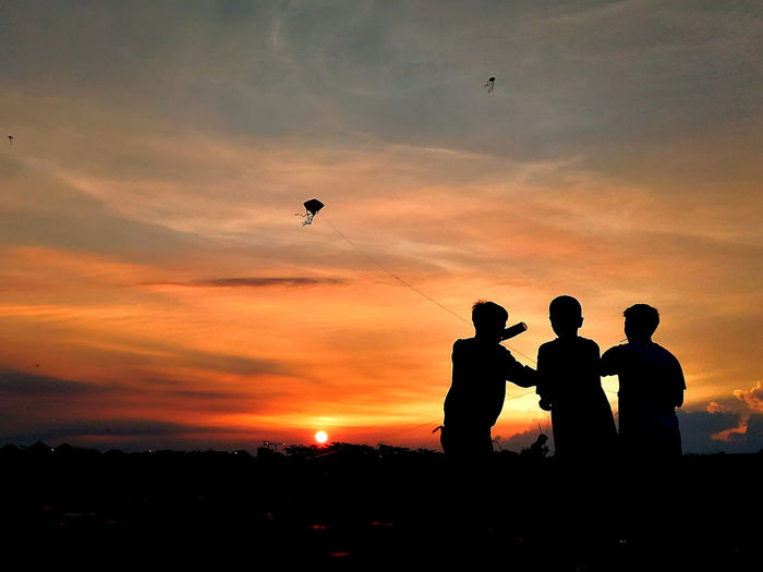 Friendship Kite Beauty In Nature Cloud - Sky Flying Friendship Leisure Activity Lifestyles Men Nature Orange Color Outdoors People Real People Scenics Silhouette Sky Standing Sunset Togetherness