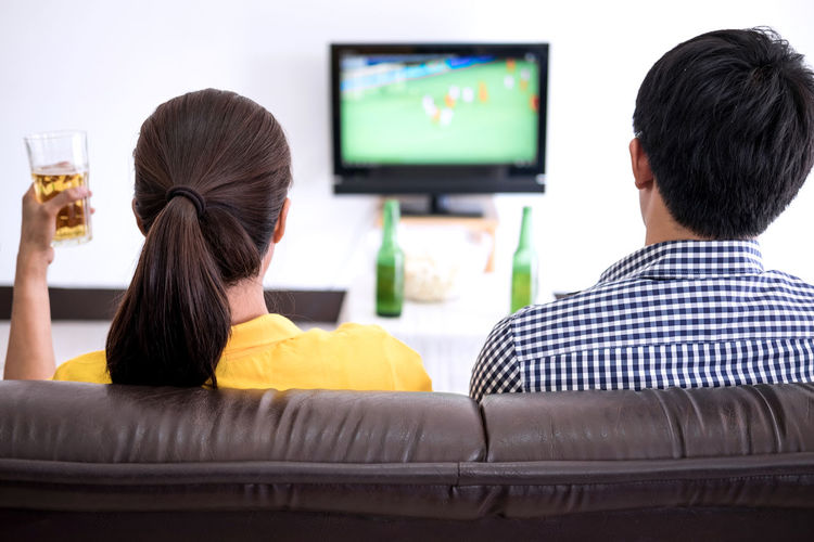 Rear View Of Men And Women Watching Soccer On Sofa