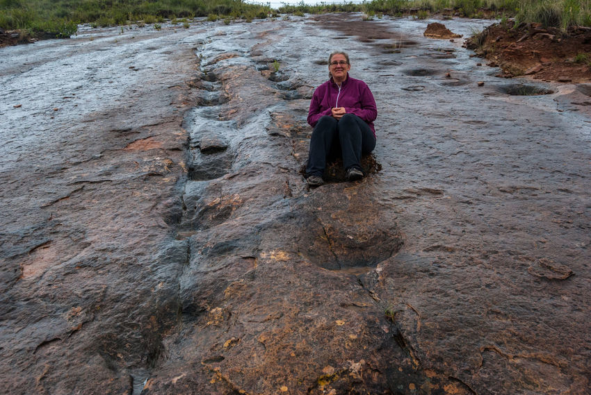 Sitting in Dino prints Bolivia Dinosaur FootPrint Adult Day Front View Full Length Leisure Activity Lifestyles Looking At Camera Nature One Person One Woman Only Outdoors People Portrait Real People Rock - Object Sitting Torotoro Women
