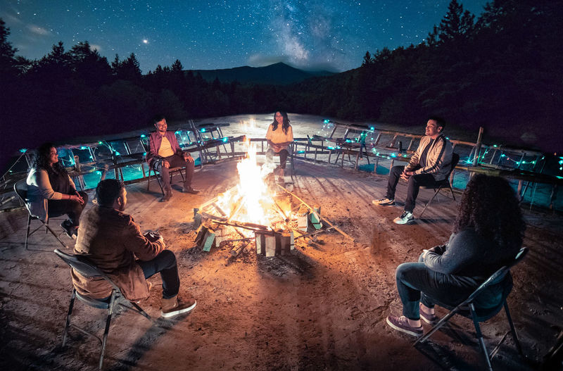 People sitting by bonfire against mountain at night
