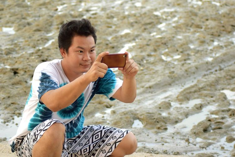 High angle view of young man photographing with mobile phone while crouching at beach