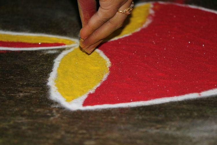 Cropped hand of woman making rangoli on floor
