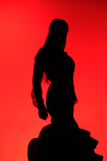 Rear view of silhouette woman standing against red background