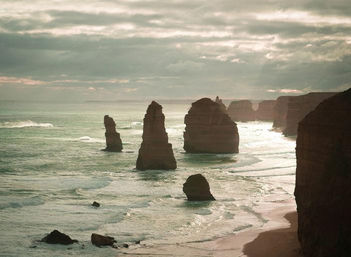 Twelve apostles in sea against sky