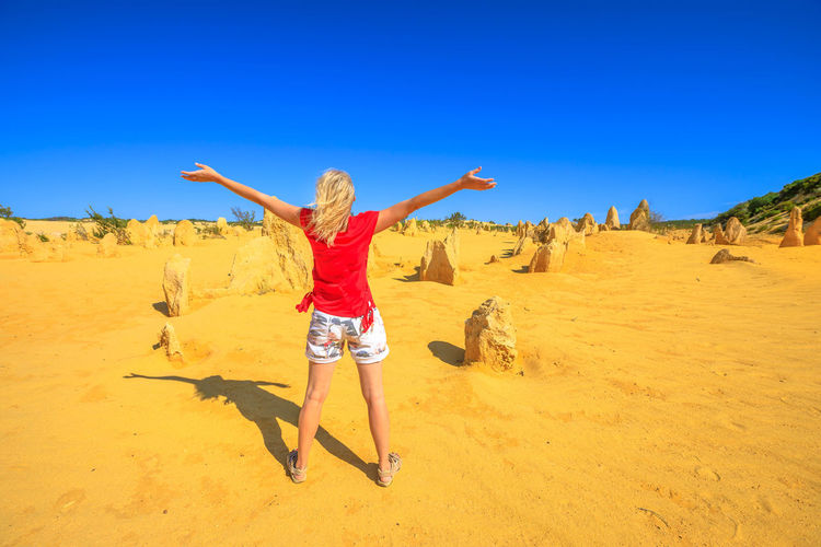 Rear view of woman with arms outstretched standing on land against sky