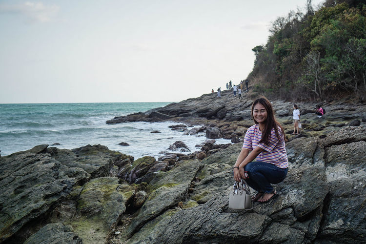 Portrait of smiling woman crouching on rock by sea against sky