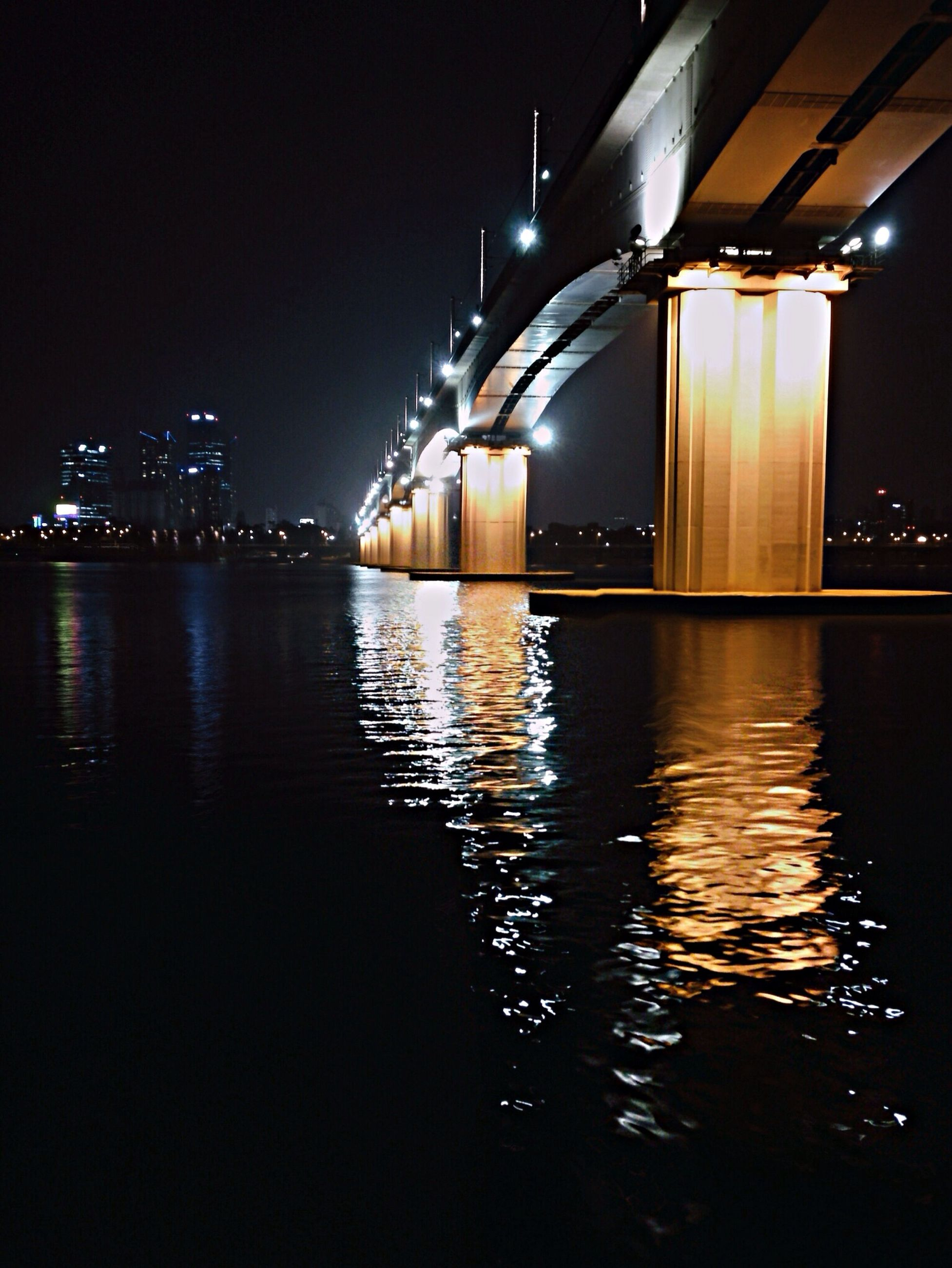 illuminated, night, water, architecture, built structure, reflection, waterfront, building exterior, river, city, bridge - man made structure, dark, sky, no people, connection, rippled, building, outdoors, lighting equipment, tranquility