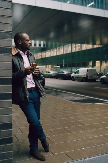 Full length of man standing on street in city