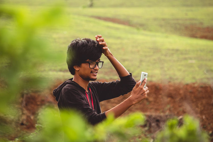 Side view of young man using mobile phone on field