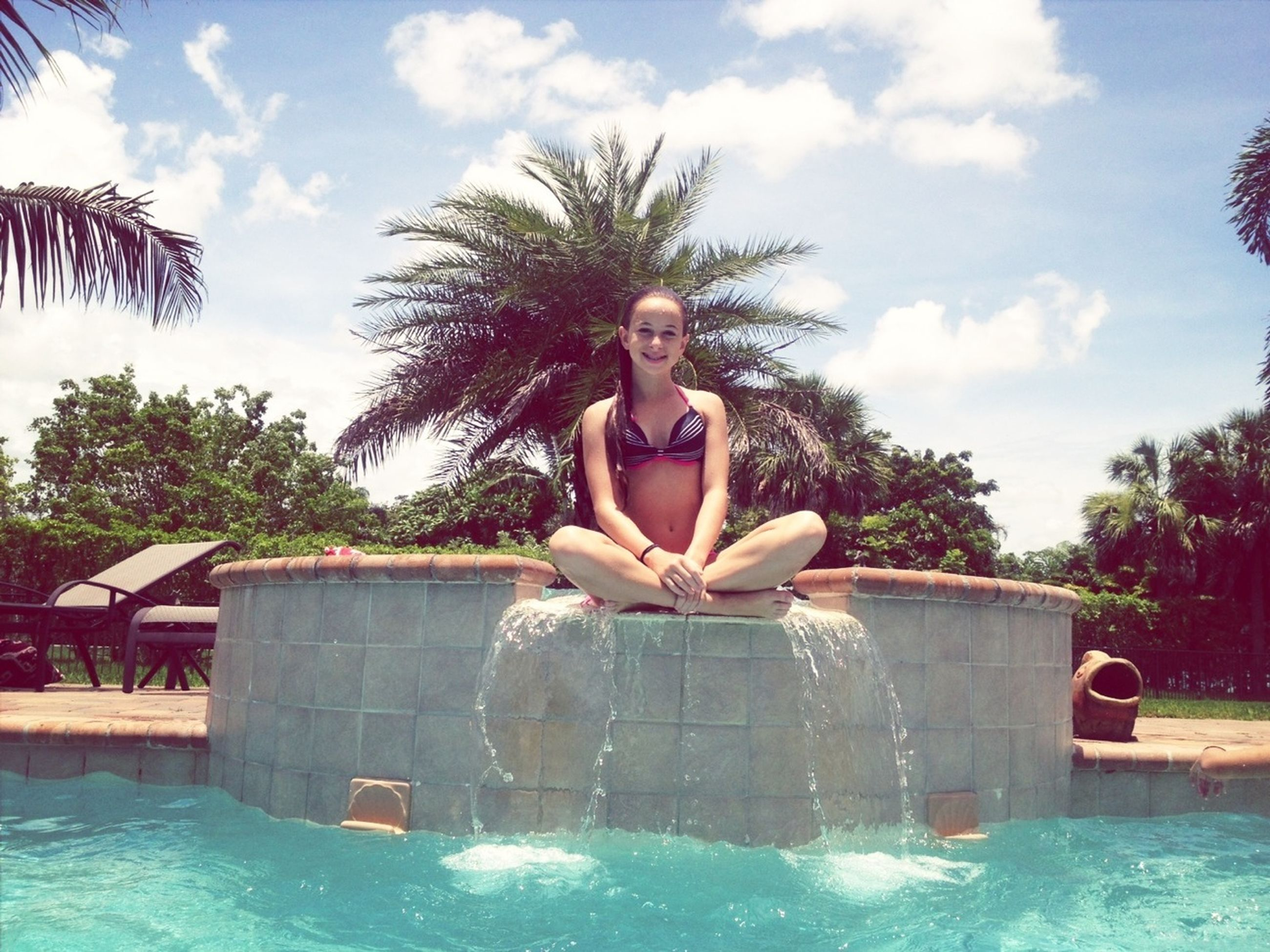 water, swimming pool, sky, tree, palm tree, young adult, person, leisure activity, lifestyles, young women, cloud - sky, waterfront, sea, full length, cloud, bikini, day, sunglasses