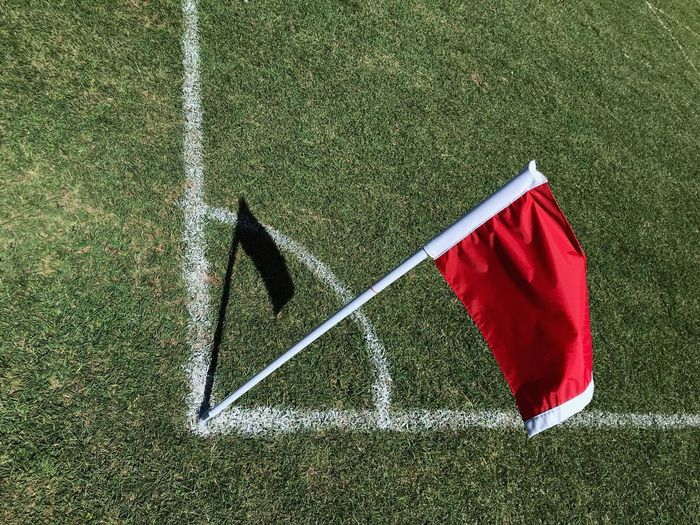 High angle view of red flag on soccer field during sunny day