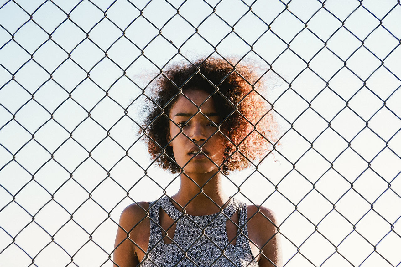 Portrait of young woman looking through chainlink fence