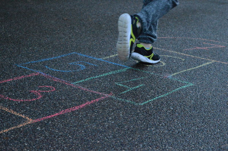 Low section of person playing hopscotch on footpath