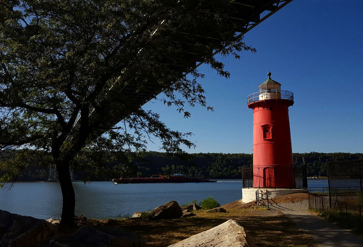 Lighthouse Coastline Tranquil Scene Water Guidance Redlighthouse River View Red Blue Sky Parkside Riverside NYC Photography Nycphotography New York City Newyorkcity Manhattan Manhattanlighthouse Rocky Coastline Outdoors Tower Tree Building Exterior Built Structure