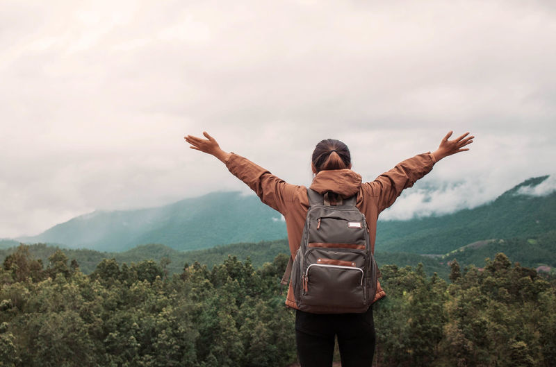 Arms Outstretched Arms Raised Beauty In Nature Casual Clothing Cloud - Sky Day Gesturing Landscape Leisure Activity Lifestyles Mountain Nature One Person Outdoors People Real People Rear View Scenics Sky Standing Three Quarter Length Tree Women Young Adult Young Women
