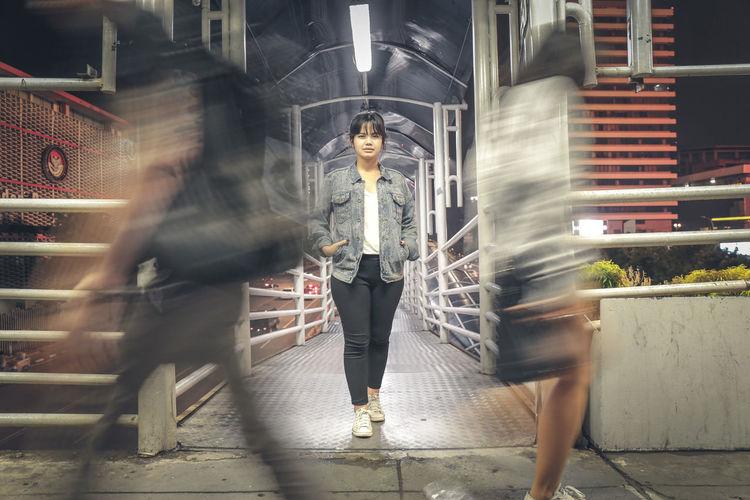 Blurred motion of women walking on bridge at night