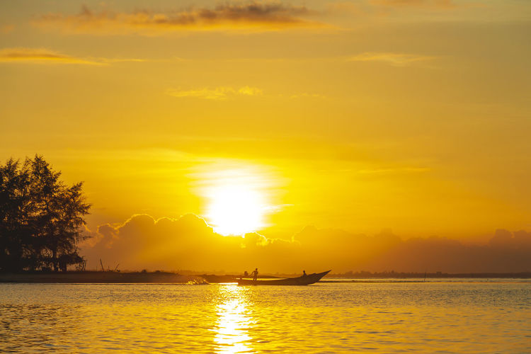 Silhouette of fisherman catching fish early in the morning at laem ta chi, pattani, thailand