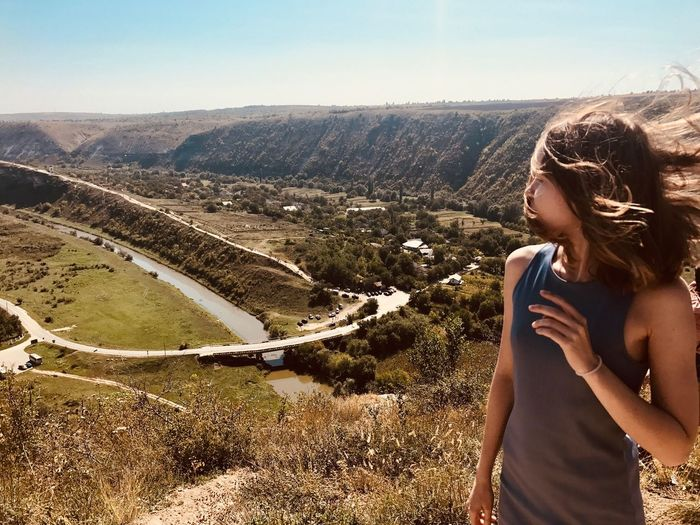 Young woman looking at landscape against sky