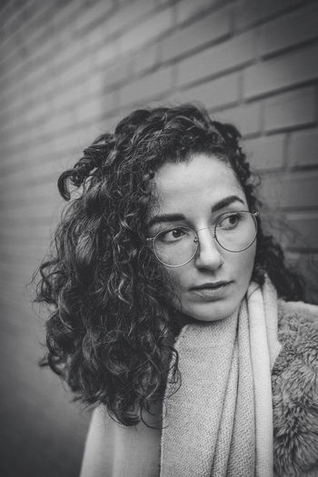 Portrait of Young woman with glasses standing in front of wall Autumn Glasses Winter Beautiful Woman Close-up Coat Cold Curly Hair Day Front View Home Interior Indoors  Leisure Activity Lifestyles Looking At Camera One Person Portrait Real People Scarf Young Adult Young Women
