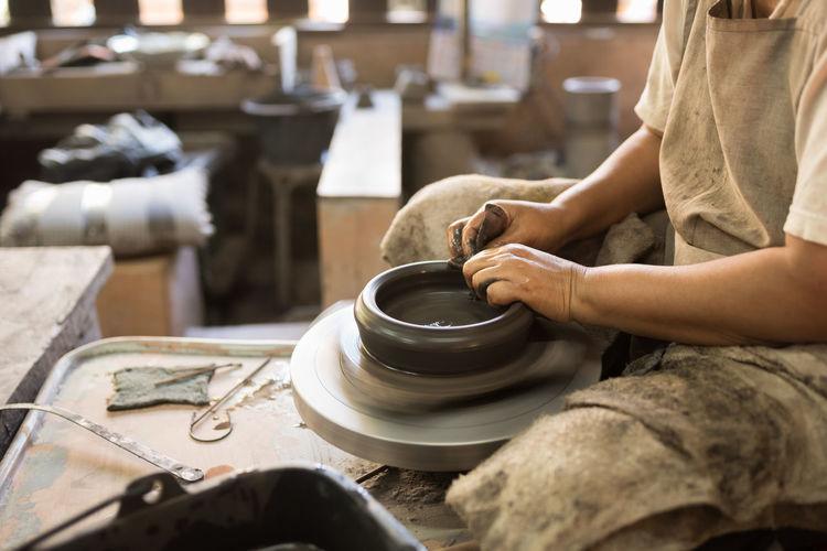 Midsection Of Potter Making Pot On Wheel At Workshop