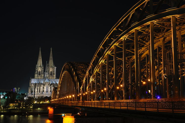 Hohenzollern bridge by cologne cathedral in city at night