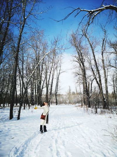 Man on snowy field against sky during winter