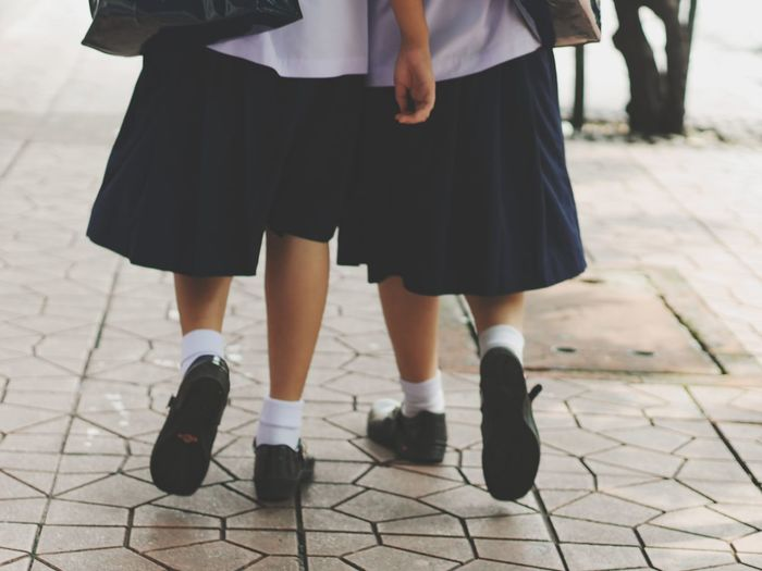 Low section of girls walking on street