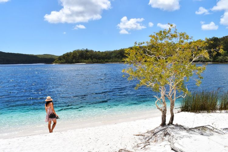 Water Tree One Person Sky Beauty In Nature Plant Nature Leisure Activity Real People Lifestyles Tranquility Tranquil Scene Day Scenics - Nature Standing Cloud - Sky Full Length Women Beach Outdoors