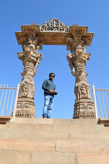 Low angle portrait of man standing at entrance of temple against clear blue sky