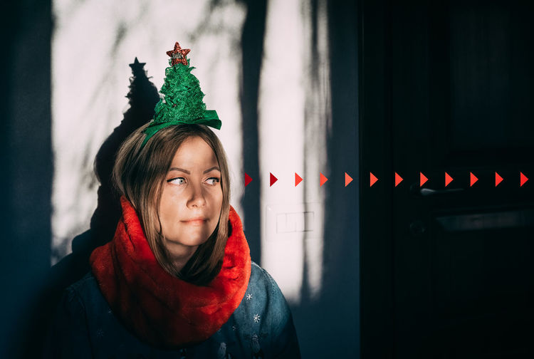 Close-up woman wearing christmas decoration in darkroom