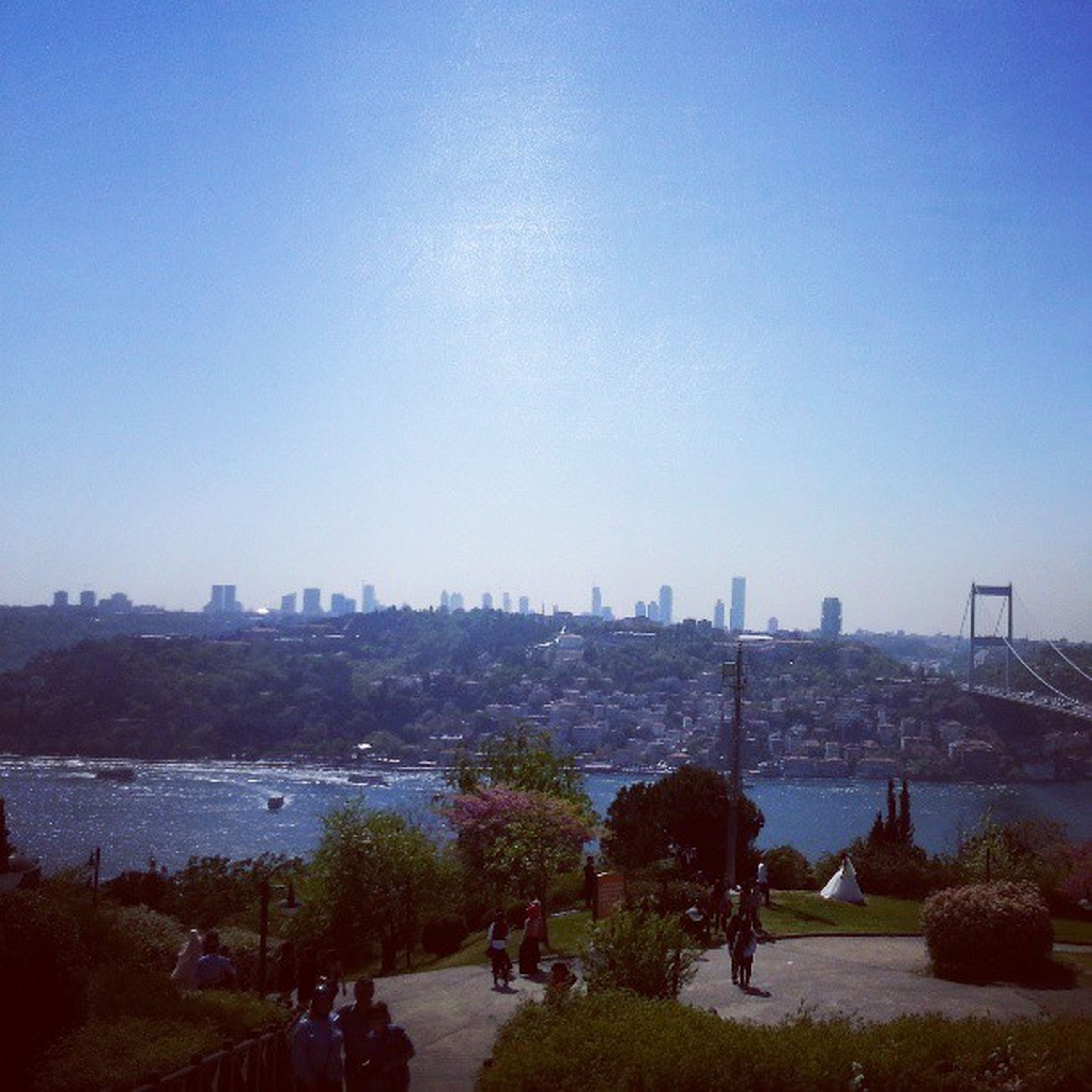 clear sky, copy space, architecture, built structure, water, city, building exterior, cityscape, blue, river, tree, sea, city life, travel destinations, bridge - man made structure, incidental people, outdoors, day, large group of people, capital cities