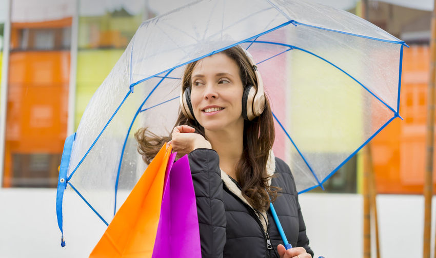 Smiling Woman Holding Umbrella And Shopping Bags